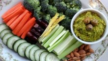 Hummus with broccoli, carrot, dates, celery, almonds, and cucumbers. Green olives garnish the dip.