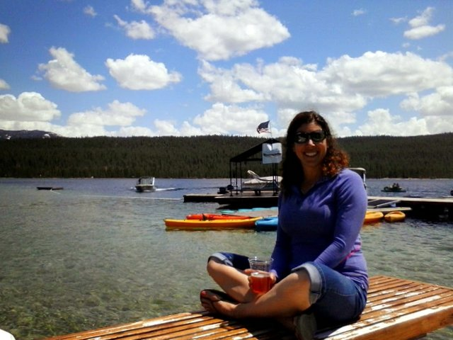 Susan enjoys the pure mountain sunshine while sitting on the dock after the race.